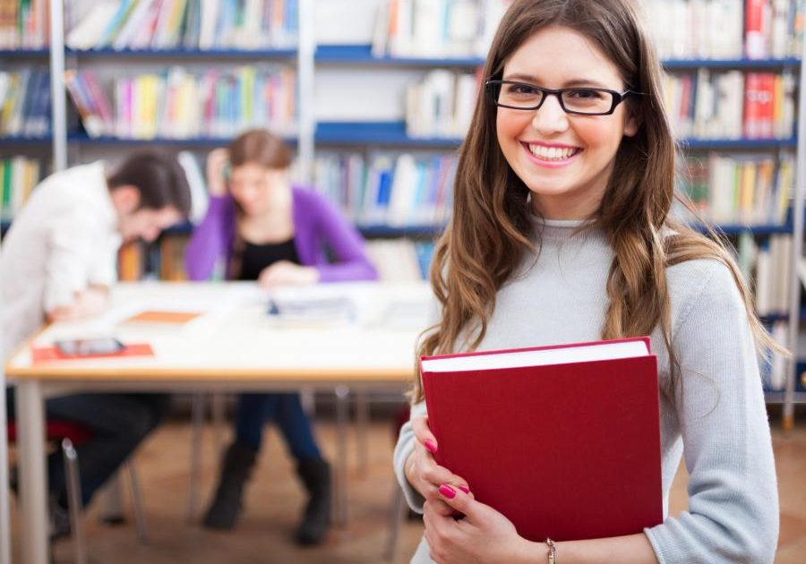 girl-carrying-red-textbook-in-library-near-table